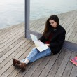 Young asian tourist woman look city map sitting on wooden pier, stylish tourist girl resting after long walk in new country studying a map — Zdjęcie stockowe #60465377