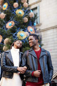 Laughing couple on christmas vacation walking in the city, beautiful young couple having fun walking on vacation holidays, romantic couple walk on christmas tree background on big square — Stock Photo