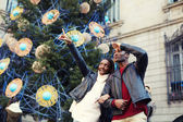 Charming woman pointing with he finger something interesting, romantic couple walk on christmas tree background on big square, laughing couple on christmas vacation walking in the city — Fotografia Stock