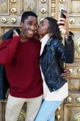 Stylish couple having fun making self portrait picture on digital camera of mobile phone, woman kissing boyfriend on the cheek photographing themselves with smartphone, couple in love on san valentine — Stock Photo