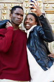 Portrait of a young attractive couple holding a smartphone and taking a selfie self portrait of themselves fooling around, young couple in love, happy couple taking self-portrait picture during travel — Stock Photo