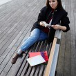 Vacation holiday in Barcelona, young female traveler sitting on wooden bench read some book, Chinese student girl reading book sitting in sea port on wooden pier, travel and leisure concept — Stock Photo #60531189