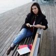 Beautiful girl holding an open book sitting on wooden bench near artificial lake, tourist woman resting after walk in new city reading some book, attractive asian girl at leisure time outdoors — Stock Photo #60531197