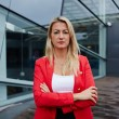 Caucasian businesswoman with arms crossed standing against her office building looking to the camera, blond hair executive business woman dressed in red jacket standing near skyscraper office building — Stock Photo #60540717