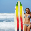 Young surfer girl standing with surfboard on the beach, beautiful hot bikini model on summer travel vacation engage water sports, teenager girl in swimsuit holding her surfboard smiling — Stock Photo #60540929