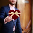 Man holding heart shaped Valentine's day gift — Stock Photo #64460431