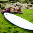 Beautiful blond girl in swimsuit relaxing after surfing lying on the beach with copy space surf board — Stock Photo #69199515