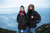 Couple of young tourists standing on top of a mountain in the cool autumn day — Stock Photo
