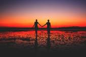 Couple in love holding hands at sunset — Fotografia Stock