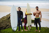 Surfers standing on the beach — Stock Photo