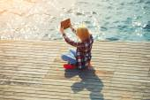 Woman taking a selfie while sitting on wooden pier — Stock Photo