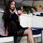 Woman dressed in black bikini relaxing in cafe — Stock Photo #73327181