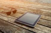 Sunglasses and digital tablet on wooden jetty — Stock Photo