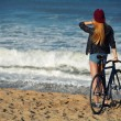Hipster girl relaxing on the beach wit bicycle — Stock Photo #73330357