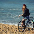 Hipster girl relaxing on the beach wit bicycle — Stock Photo #73330383