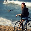 Hipster girl relaxing on the beach with bicycle — Stock Photo #73330407
