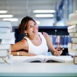 Asian smiling student  in university library — Stock Photo #73330997