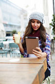 Beautiful young woman with tablet in cafe — Stock Photo