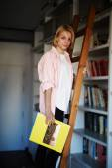 Vrouwelijke ontwerper staande op bibliotheek ladder — Stockfoto