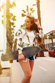 Hipster holding skateboard and standing on palm road — Stock Photo
