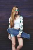 Teenage girl in sunglasses holding skateboard — Стоковое фото