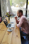 Male freelancer connecting to wireless in cafe — Fotografia Stock