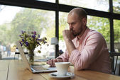Male freelancer working in coffee shop — Stock Photo
