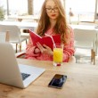 Attractive creative freelancer read notebook while sitting at wooden table with laptop laptop computer and cellphone — Stock Photo #77287844