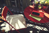Terrace table with book and mobile phone at sunny beautiful day — Stock Photo