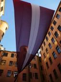 Huge Latvian Flag between old buildings — Stock Photo