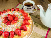 Honey cake with strawberry on top and tea — Stock Photo