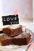 Chocolate brownies dusted with icing sugar on plate  — Stock Photo