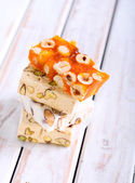 Honey and different sorts of nut nougat — Stock Photo