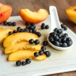 Peach slices and blueberries in spoon on a white board — Stock Photo #52763077