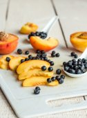 Slices of juicy peaches and blueberries on a white board — Stock Photo
