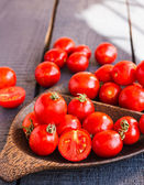 Red juicy tomatoes cherry in brown wooden plate  — Stock Photo