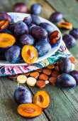 Juicy blue plum slices on a wooden board — Stock Photo