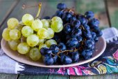 Twig  of green and blue grapes on a plate — Stock Photo