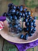 Twig of blue grapes in a glass on a plate — Stock Photo