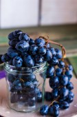 Twig of blue grapes in a glass, closeup — Stockfoto