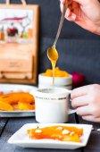 Pour a teaspoon honey in ceramic ware, baked pumpkin, hands — ストック写真