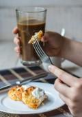 Mangiare frittelle di ricotta con panna acida per la colazione, le mani — Foto Stock