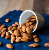 Scatter nuts almonds in a white bowl on blue napkin — Stock Photo