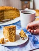 Eating honey cake with sour cream and nuts, hand — Stock Photo