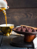 Truffle chocolates, pouring coffee into a cup — Stock Photo
