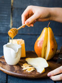 Fresh juicy pear with cheese and honey on a wooden board — Stok fotoğraf