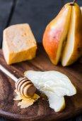 チーズと木の板の上に蜂蜜と新鮮なジューシーな梨 — ストック写真