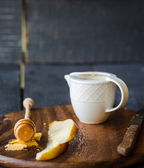 Fresh juicy pear with cheese and honey on a wooden board — Stock Photo