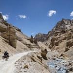 Couple riding on bike among jagged mountains — Stock Photo #59698993