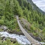 Suspension bridge over fast mountain river — Stock Photo #59699687